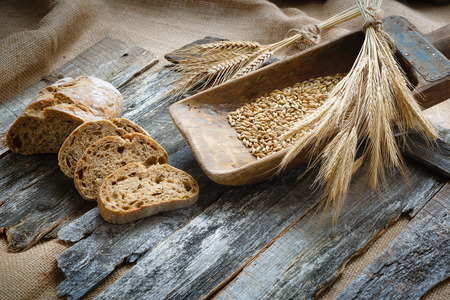 ciabatta: Fresh bread and wheat on the wooden boards Stock Photo