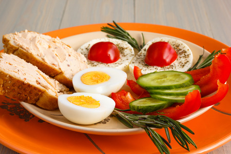 Healthy breakfast with eggs, bread, cottage cheese and fresh vegetables on the orange tableware