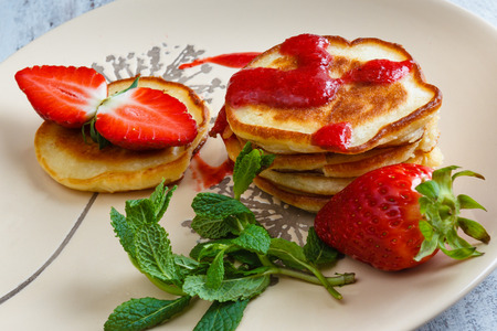 A stack of pancakes with strawberries and fresh mint