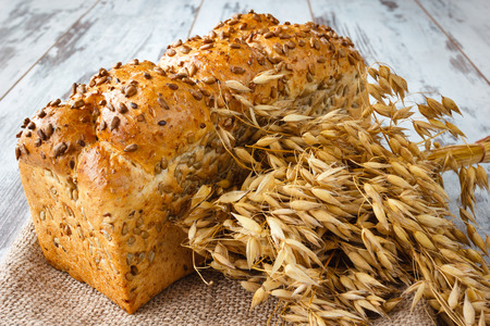 Fresh bread with sunflower seeds and ears on burlap