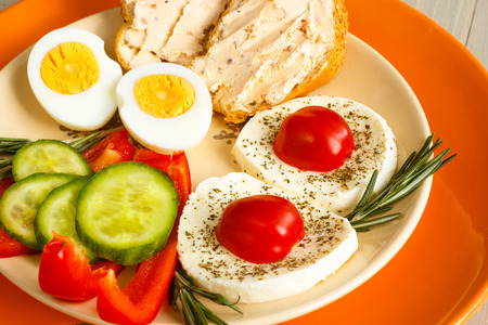 Healthy breakfast with eggs, cheese mozzarela, bread, rosrmary and fresh vegetables