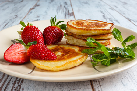 A set of pancakes with strawberries and peppermint in rustic style