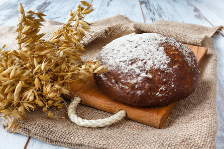 Dark bread with crumbs and ears on sacking background