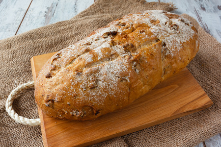 Fresh bread with walnut  on wooden board