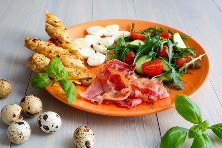 quail egg: Healthy breakfast, bekon with salad and quail egg Stock Photo