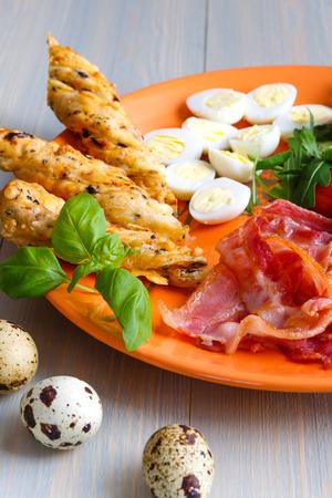 quail egg, bacon and vegetables on orange dish