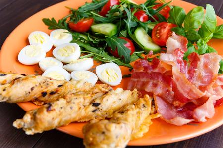 english cucumber: Healthy breakfast, bekon with salad and quail egg on orange dish