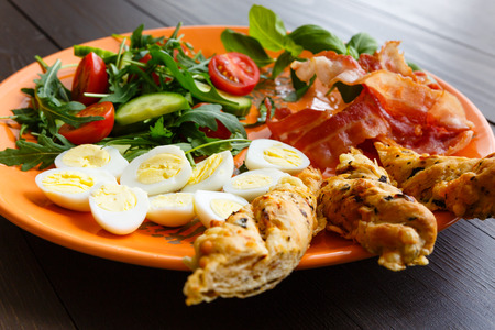 english cucumber: Closeup of boiled quail eggs with bacon and salad. Traditional english breakfast on old wooden boards