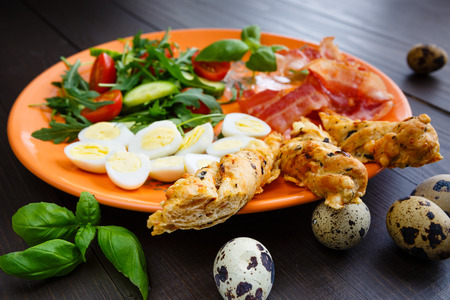 Traditional english breakfast egg, bacon, salad, homemade bread and basil