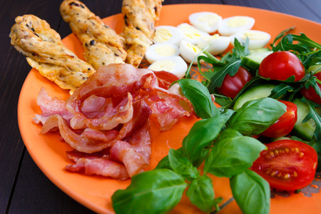 Closeup of boiled quail eggs with bacon and salad on old wooden background