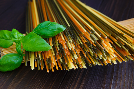 Colored italian spaghetti with basil on old wooden background