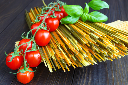 Colored italian spaghetti with mini tomatoes and basil Banque d'images