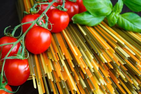 Colored spaghetti pasta with basil and mini tomatoes