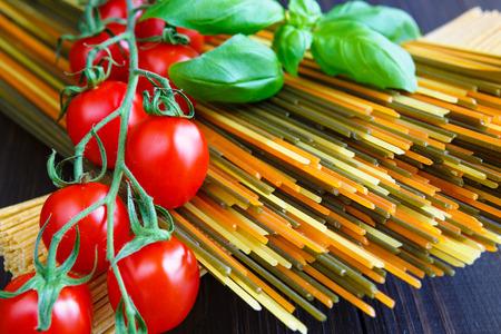 Colored italian spaghetti pasta with basil and tomatoes