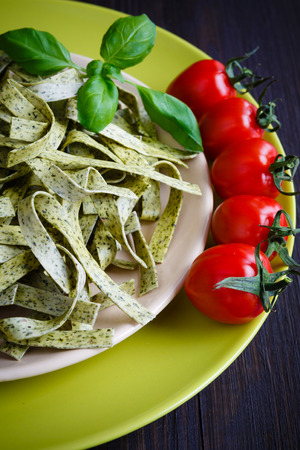 Pasta tagliatelle with spinach, basil and cherry tomatoes on light green dish Banque d'images
