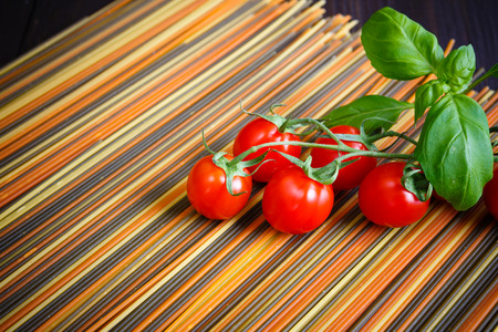 Colored italian spaghetti with mini tomatoes and basil closeup Banque d'images