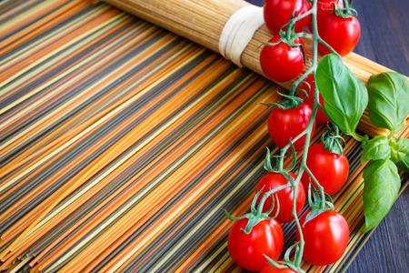 Wholegrain colored italian spaghetti with mini tomatoes and basil