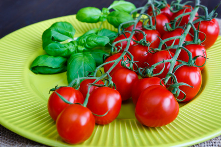 Cherry tomatoes with basil on the light green plate