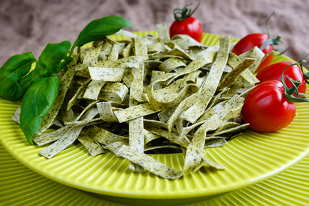 Pasta tagliatelle with spinach basil and cherry tomatoes on light green dish