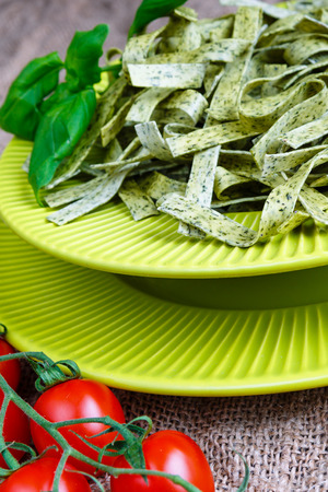 Pasta tagliatelle with spinach, basil and cherry tomatoes on light green tableware