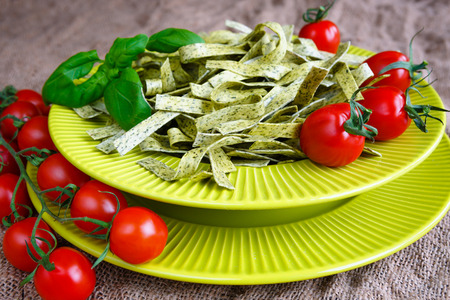 Pasta tagliatelle with spinach, basil and cherry tomatoes on light green textured plate