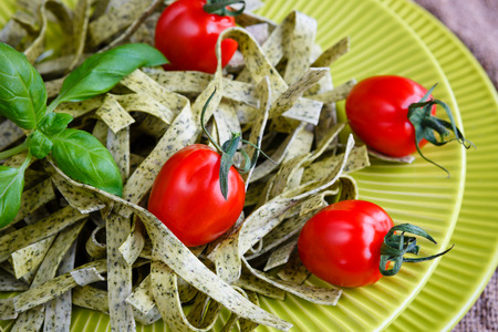 Closeup italian pasta tagliatelle with spinach, basil and cherry tomatoes on light green dish