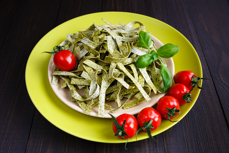 Pasta tagliatelle with spinach, basil and cherry tomatoes on on dark wooden background Banque d'images