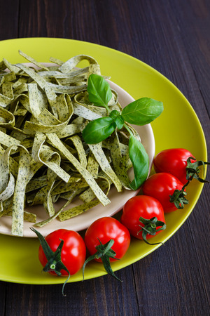Pasta tagliatelle with spinach, basil and cherry tomatoes on old wooden table