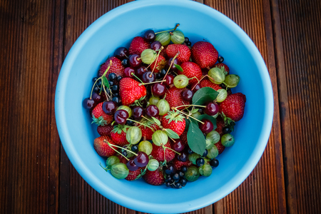 Mix of fresh and juicy berries from the summer garden in the blue dishes