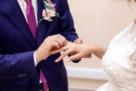 the groom in a dark blue suit carefully puts the ring on the bride's hand on the ring finger