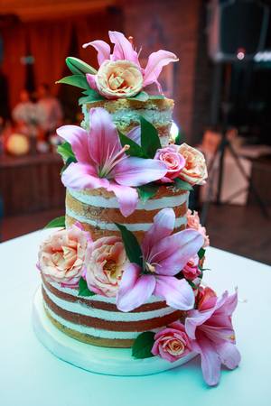Big wedding rustic cake with real natural living roses and lily Stock Photo