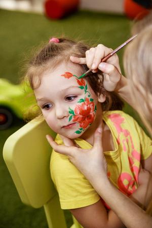L'animateur dessine un dessin de maquillage pour enfants sur le visage d'un enfant