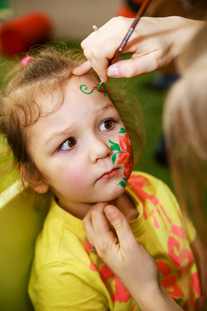 The animator draws a childrens makeup drawing on the face of a child