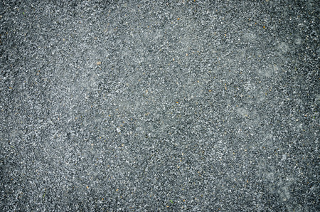 granit: Grainy asphalt on a street, with visible sand and gravel, texture.