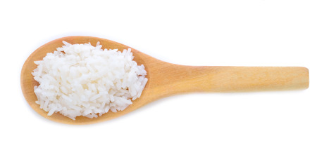 processed grains: rice in a wooden spoon placed on white background