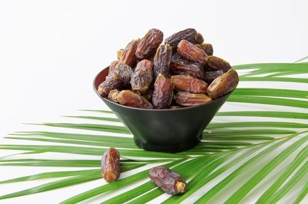 quran: Plato lleno de fruta de fechas aisladas sobre fondo blanco