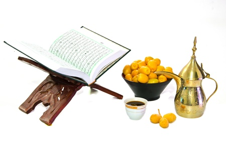 the holy quran and  arabic coffee with date fruit on white background photo