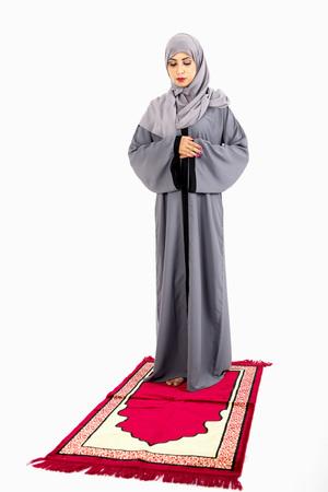 Arab Muslim woman praying on a praying carpet. Isolated on white background Stock Photo