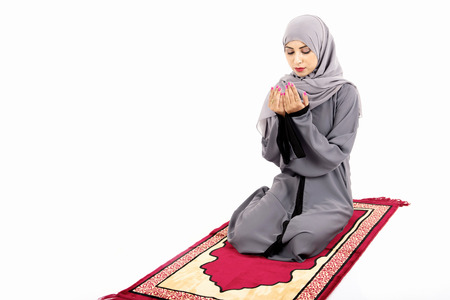 Arab Muslim woman praying on a praying carpet. Isolated on white background Stock Photo