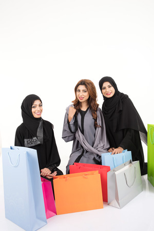 Beatuful Arab females after shopping on white background