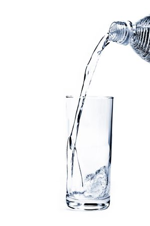 Mineral Water being poured into a glass from plastic bottle Stock Photo