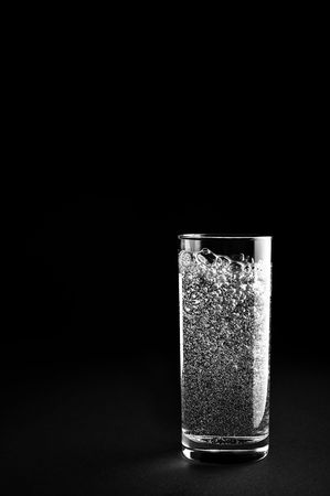 Glass of mineral water is isolated against a black background