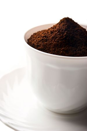 Pile of fresh ground coffee in a cup is isolated against a white background