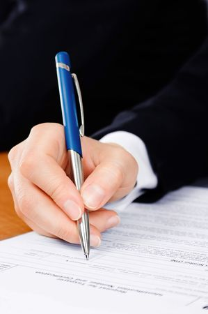law report: Pen in mans hand, filling the tax form