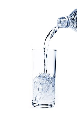 flowing water: Pouring water from a bottle into a glass against a white background Stock Photo