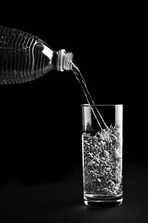 Mineral water being poured into a glass is isolated against a black background