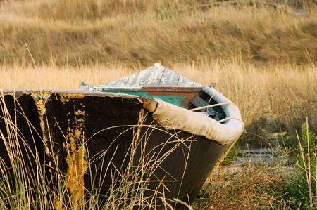 useless: Old wooden fish-boat abandoned in a grass field Stock Photo
