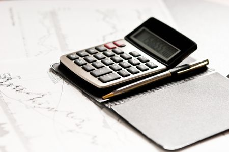 Close-up of a calculator, stock charts and ballpen Stock Photo