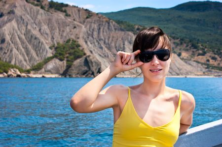 Pretty girl holding glasses while sailing near the sea coast Archivio Fotografico