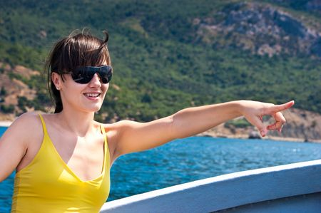 Pretty girl pointing by finger while sailing near the coastline